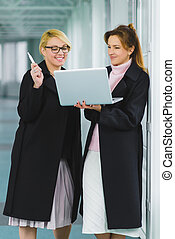 Two smiling Attractive businesswoman using laptop at office lobby