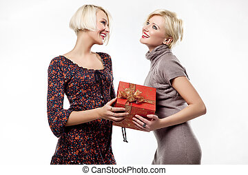 Two smiling blond beauties holding a christmas present