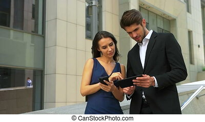 Two smiling business partners using mobile phone and tablet in the street.
