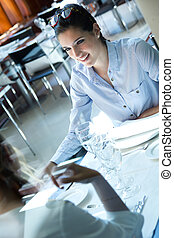 Two smiling business women have dinner at restaurant