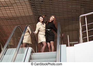 two smiling business women standing on an escalator in a modern office