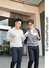 Two smiling businessmen walking and talking in the city