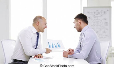 two smiling businessmen with charts in office