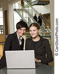 Two smiling businesswoman in front of a laptop