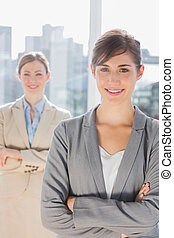 Two smiling businesswomen looking at camera with arms crossed