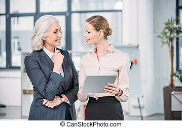 Two smiling businesswomen using digital tablet and talking in office