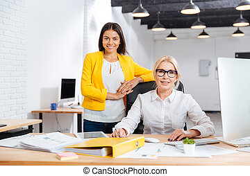 Two smiling businesswomen working together in office