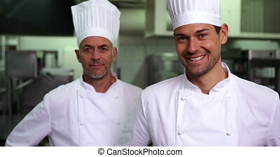 Two smiling chefs giving ok sign to camera in a commercial...
