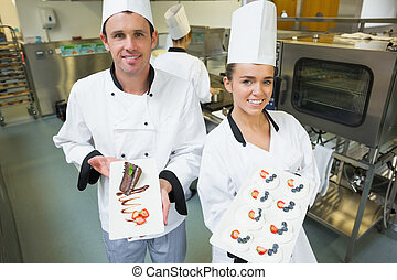 Two smiling chefs presenting dessert plates