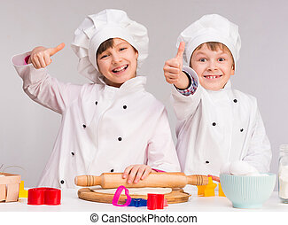 two smiling children in the kitchen with thumbs up