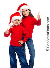 Two smiling children with thumbs up sign and Santa's hats