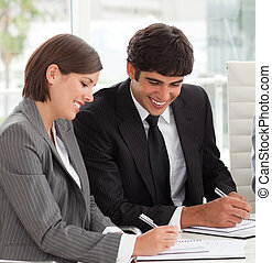 Two smiling colleagues studying sales report with their team...
