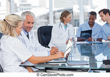 Two smiling doctors using laptop