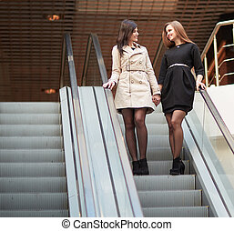 two smiling employees standing on an escalator in the business center.