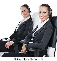 Two smiling female customer service workers. Sitting with headsets on