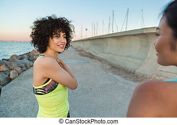 Two smiling fitness women resting after jogging outdoors