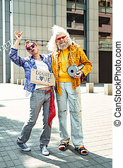 Two smiling flower-children wearing jeans singing out loud