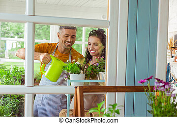Two smiling flower shop sellers watering flowers.