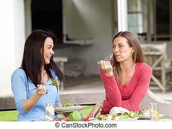 Two smiling friends enjoying lunch