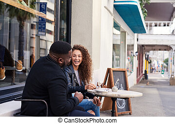 Two smiling friends talking together at a sidewalk cafe