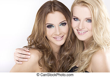 Two smiling girl friends - blond and brunette - Two smiling...