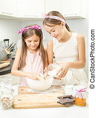 smiling girl making dough in white bowl on kitchen - Two...