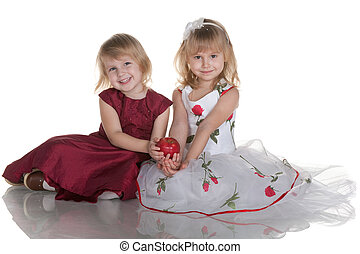 Two smiling girls holding a red apple