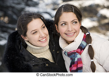 Two smiling girls playing in the winter forest