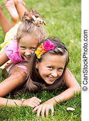 Two smiling girls playing on the summer grass