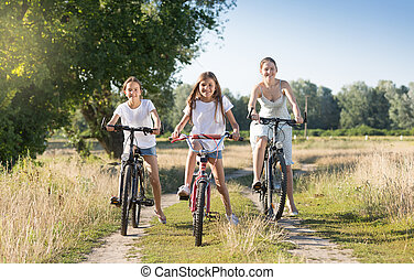 Two smiling girls riding bicycles with mother on countryside road