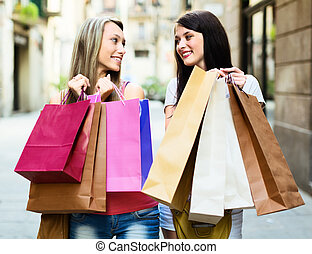 two smiling girls with shopping bags
