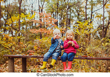 boy and girl sitting on the bench in the park