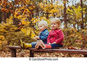 Two smiling happy kids friends, boy and girl sitting on the bench