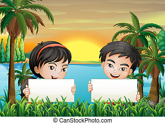 Two smiling kids at the riverbank holding two empty signboards