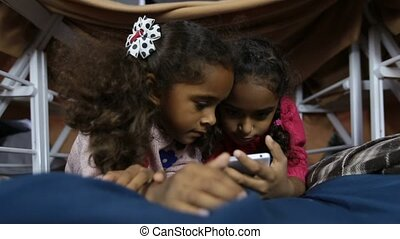 Two smiling kids watching funny pictures on phone