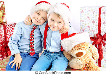 Two smiling little brothers among presents