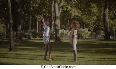 Two smiling little sisters giving high five outdoors