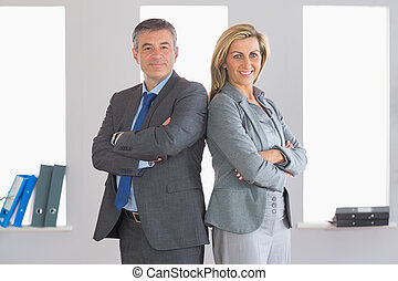 Two smiling mature businesspeople looking at camera standing firmly back to back with crossed arms at office