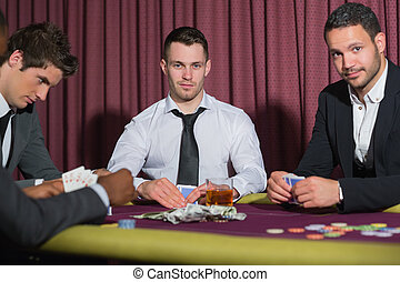 Two smiling men looking up from poker game