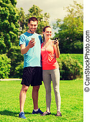two smiling people with smartphones outdoors - fitness, ...