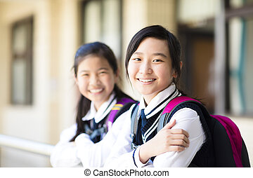 Two smiling pretty student girls  in school