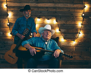 Two smiling senior country and western musicians sitting on...