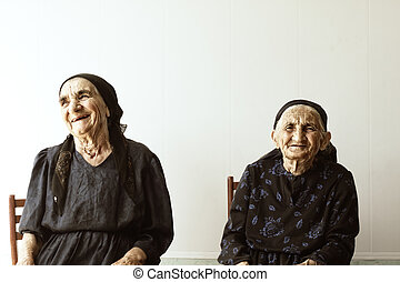 Two smiling senior women sitting outdoor against light wall