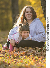 Two smiling sisters sitting on the ground in autumn park