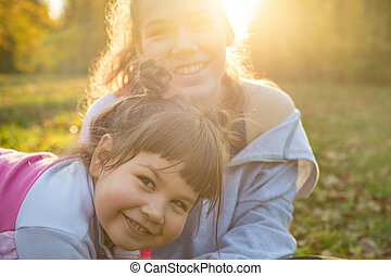 Two smiling sisters spending time in autumn park