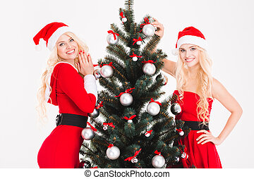 Two smiling sisters twins in santa claus dresses and hats