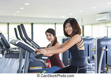 Two smiling sporty young women training on exercise bikes in gym