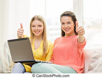 two smiling teenage girls with laptop at home