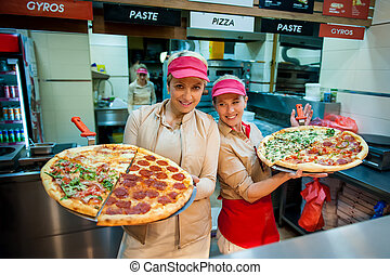 Two smiling woman workers selling pizza in fast food restaurant