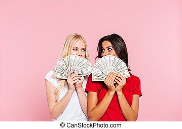 Two smiling women hiding behind the money